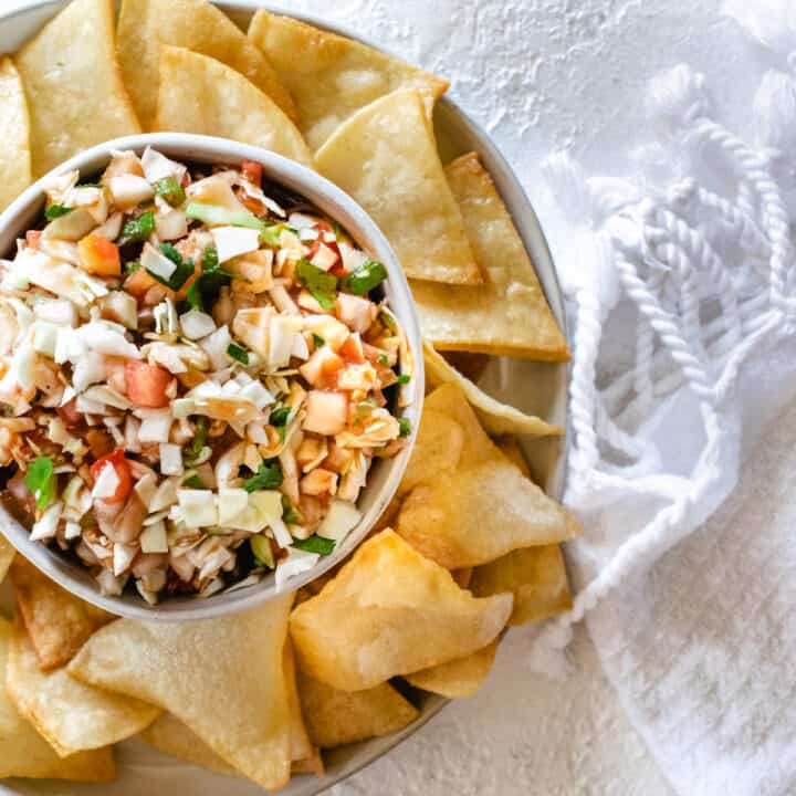 small bowl of cabbage salsa surrounded by corn tortilla chips on a plate next to white fringe towel