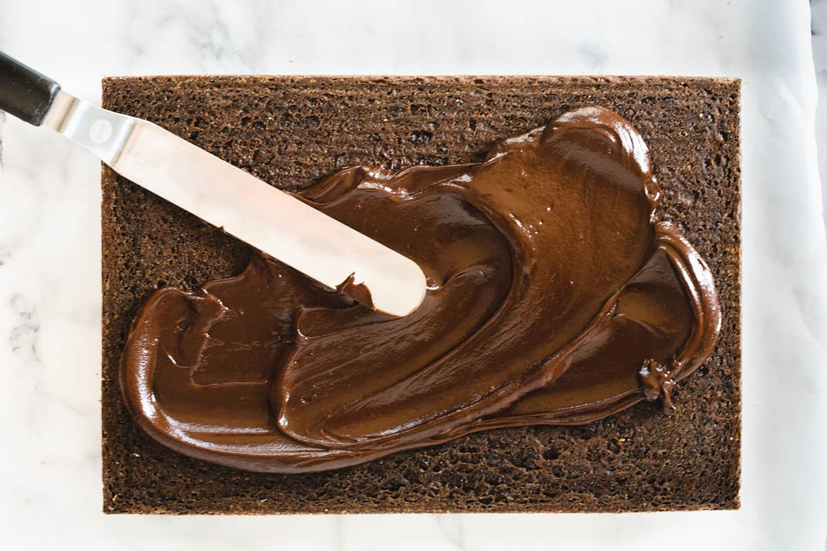 offset spatula spreading chocolate frosting over chocolate cake
