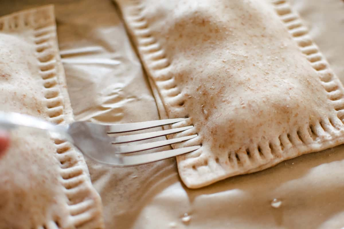 Uncooked hot pockets being pressed with the tines of a fork to seal the dough.