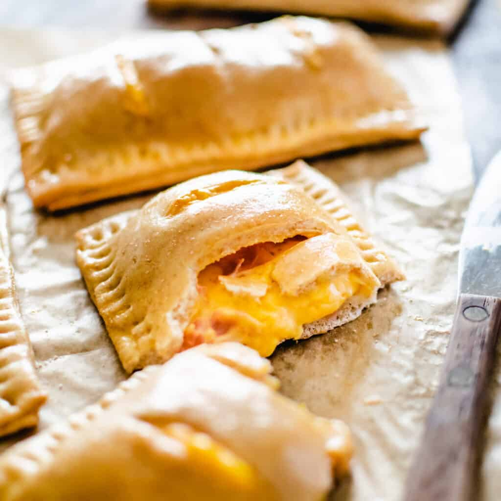 Pastry pockets filled with melted cheese sauce and pieces of ham.