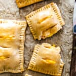 Baked rectangular pastry pouches filled with ham and cheese filling on parchment paper.