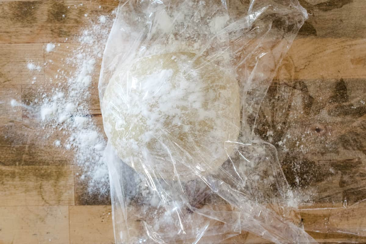 A ball of pasta dough, dusted with flour and wrapped in plastic wrap.