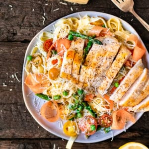 Sliced chicken breast on a bed of pasta primavera with Parmesan cheese and lemon.