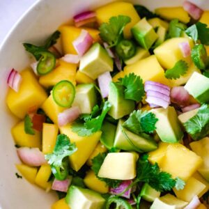 White bowl with mango, avocado, red onion and cilantro salsa