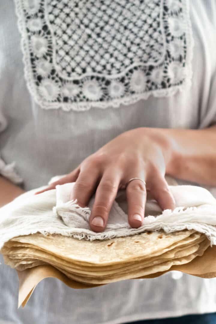 woman holding a stack of homemade soft flour tortillas