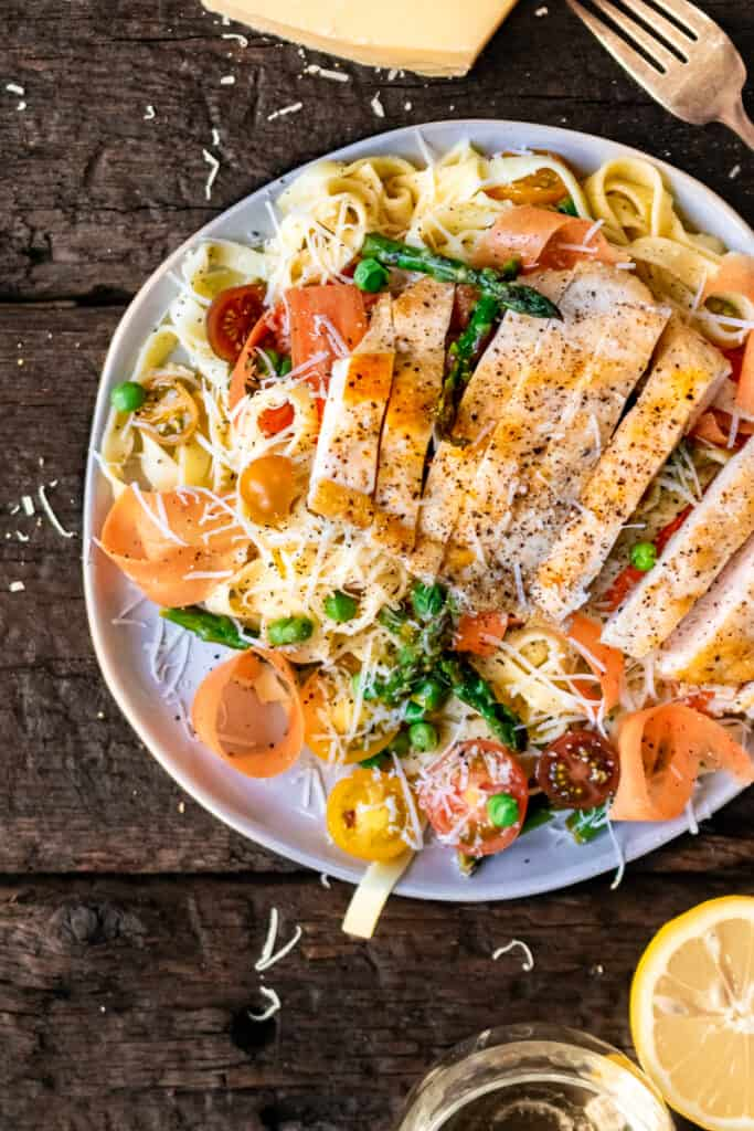 Ribbon pasta with peas, asparagus, carrots, tomatoes and sliced chicken.