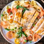 Sliced chicken breast on a bed of pasta primavera with a lemon wedge and Parmesan cheese.