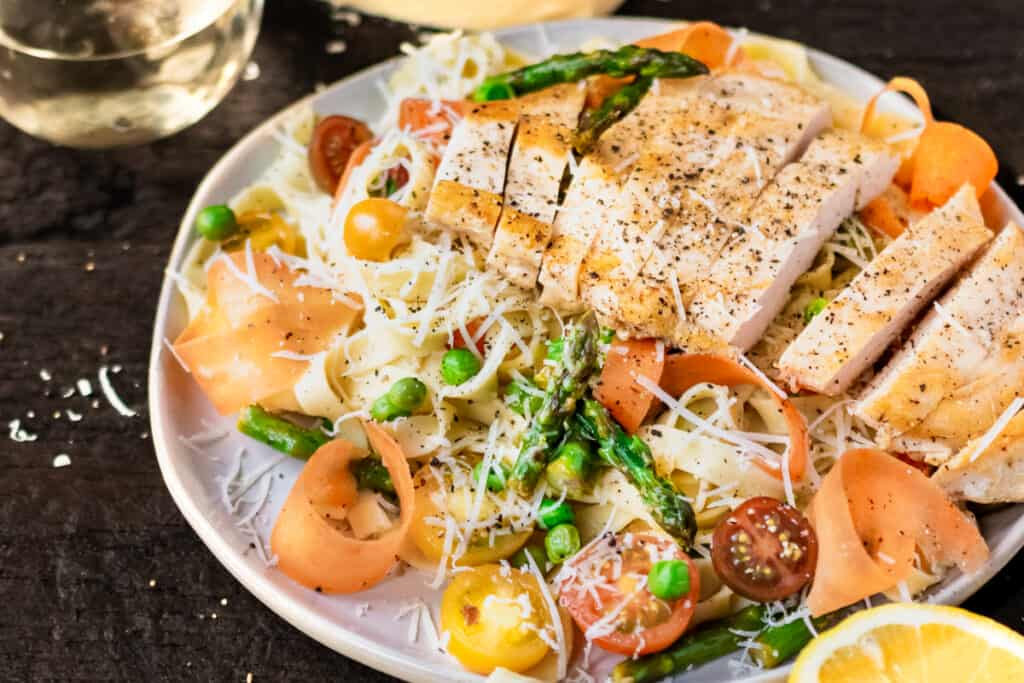 Sliced chicken breast atop a bed of pasta primavera with a lemon wedge.