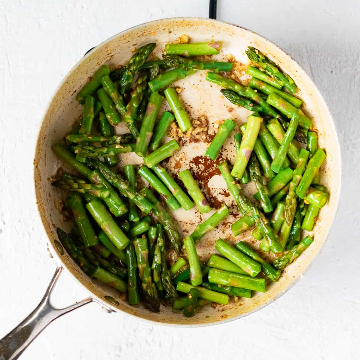 Cut green asparagus sautéing in a pan with minced garlic and butter.