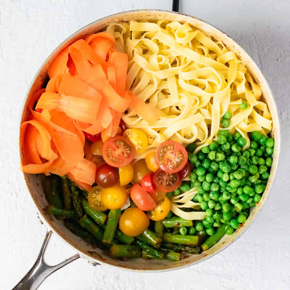 Pasta. vegetables, Parmesan and black pepper in a skillet.