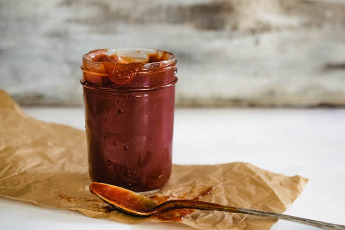 jar of homemade ketchup with spoon on brown parchment paper with distressed white wooden background