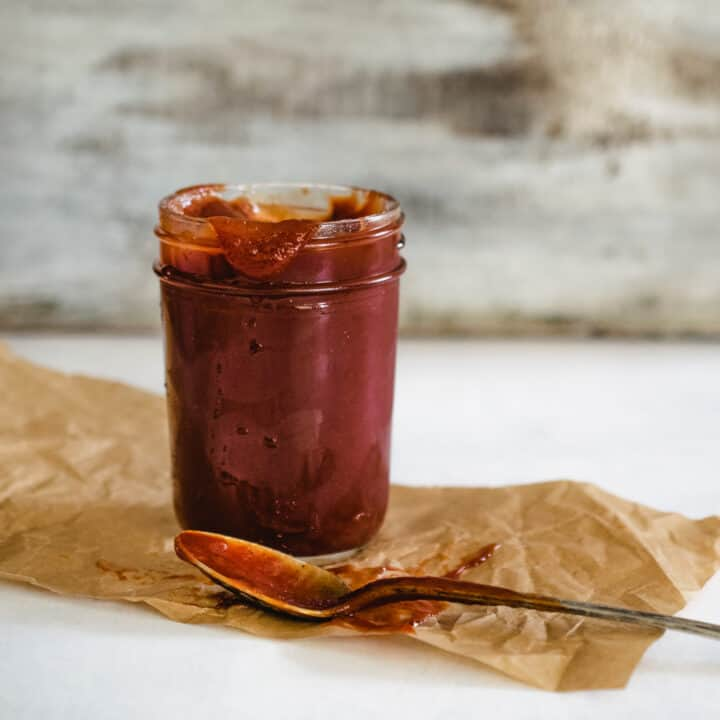 mason jar of homemade ketchup with antique spoon and distressed wooden backdrop