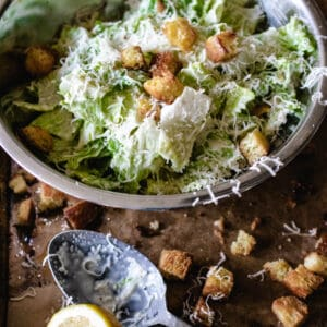 bowl of tossed caesar salad with spoon and croutons on brown surface