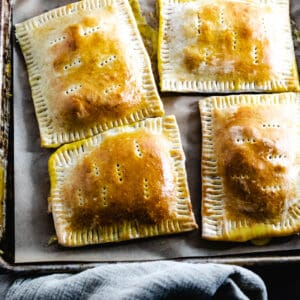 homemade ham and cheese hot pockets on metal baking sheet