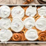 Cinnamon rolls in a pan, some with whipped cream cheese frosting on taupe cloth.
