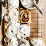 Cinnamon rolls on wire rack with cup of cream cheese icing and knife.