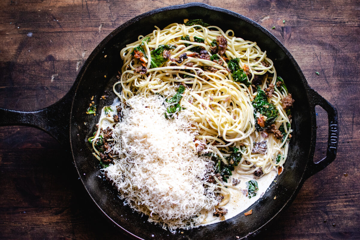 skillet of linguine, kale and sausage to be tossed with cream and Parmesan wine sauce