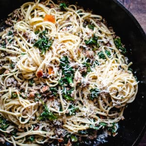 skillet of spicy sausage and kale linguine tossed with wine cream sauce and Parmesan cheese