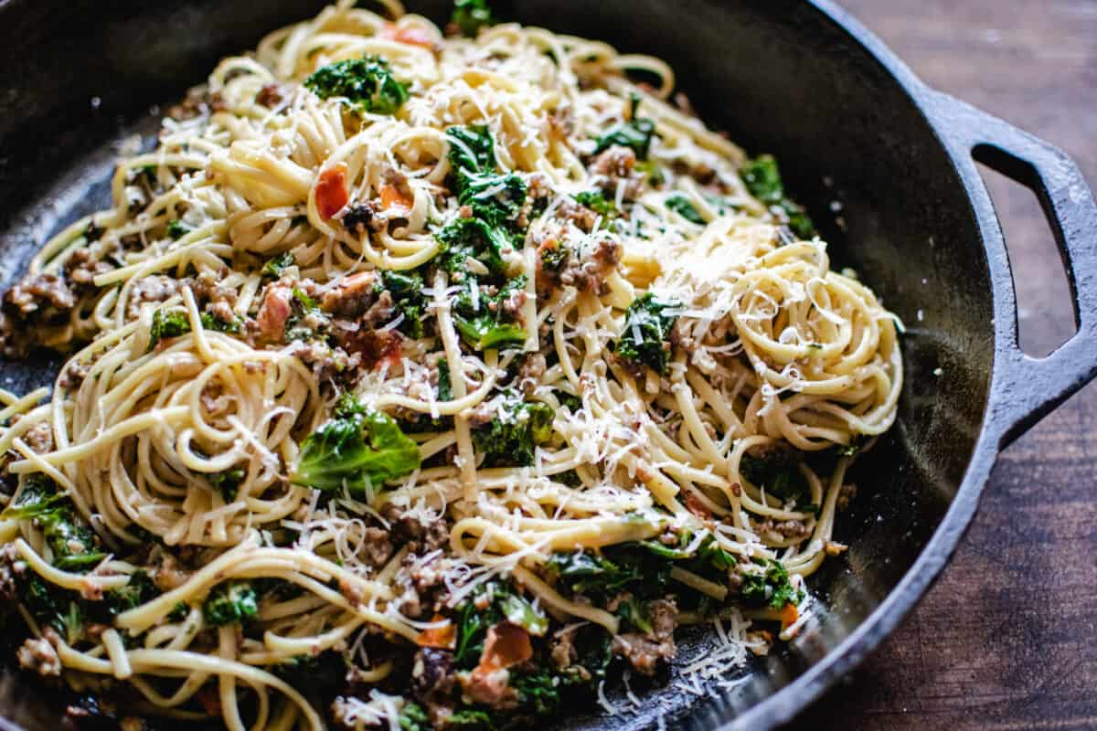 cast iron skillet of tossed ground sausage, kale and linguine pasta sprinkled with Parmesan cheese in a light wine cream sauce