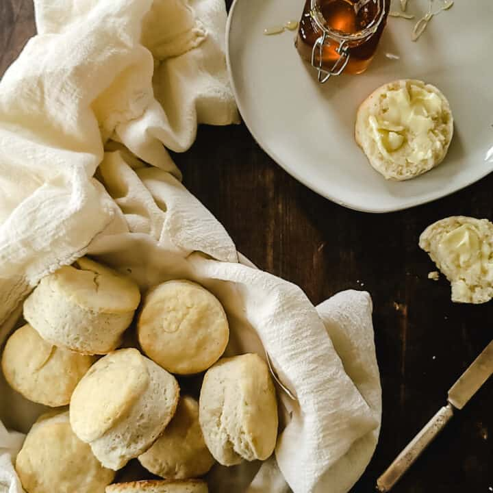 A basket of biscuits with butter and honey.