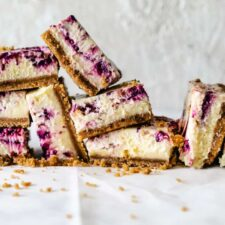 stack of cheesecake squared with berry swirls