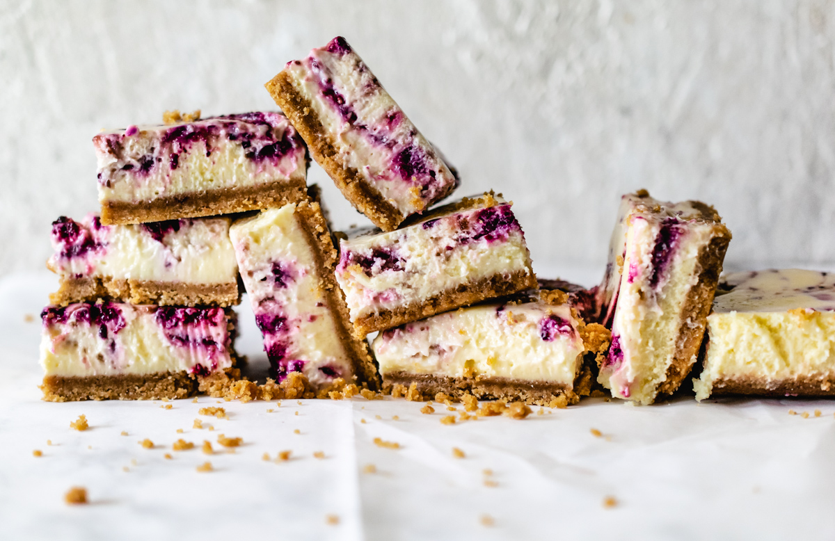 cheesecake bars swirled with a berry ribbon stacked up