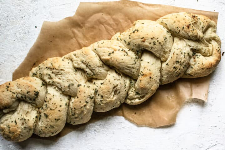 baked loaf of garlic bread shaped into a braid