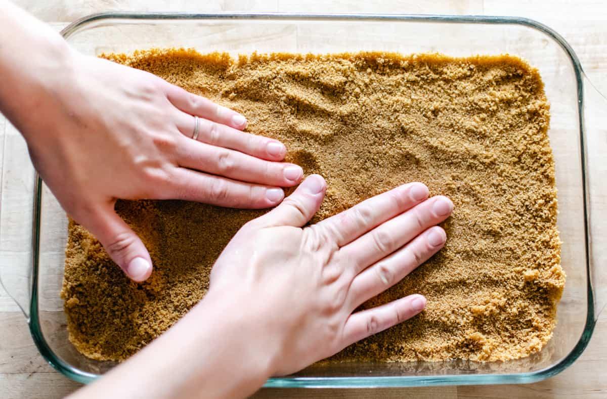 pressing graham cracker crust into glass pan