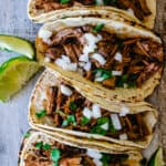 six corn tortillas with shredded beef, onion, cilantro and lime wedges on rustic wood board