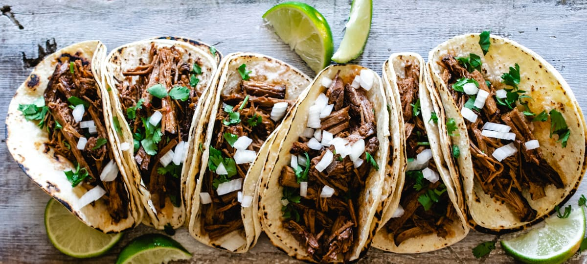 six tacos de barbacoa topped with cilantro and onion with lime wedges on rustic wood