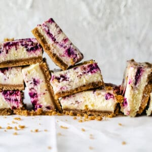 squares of berry swirled cheesecake bars stacked in a pile