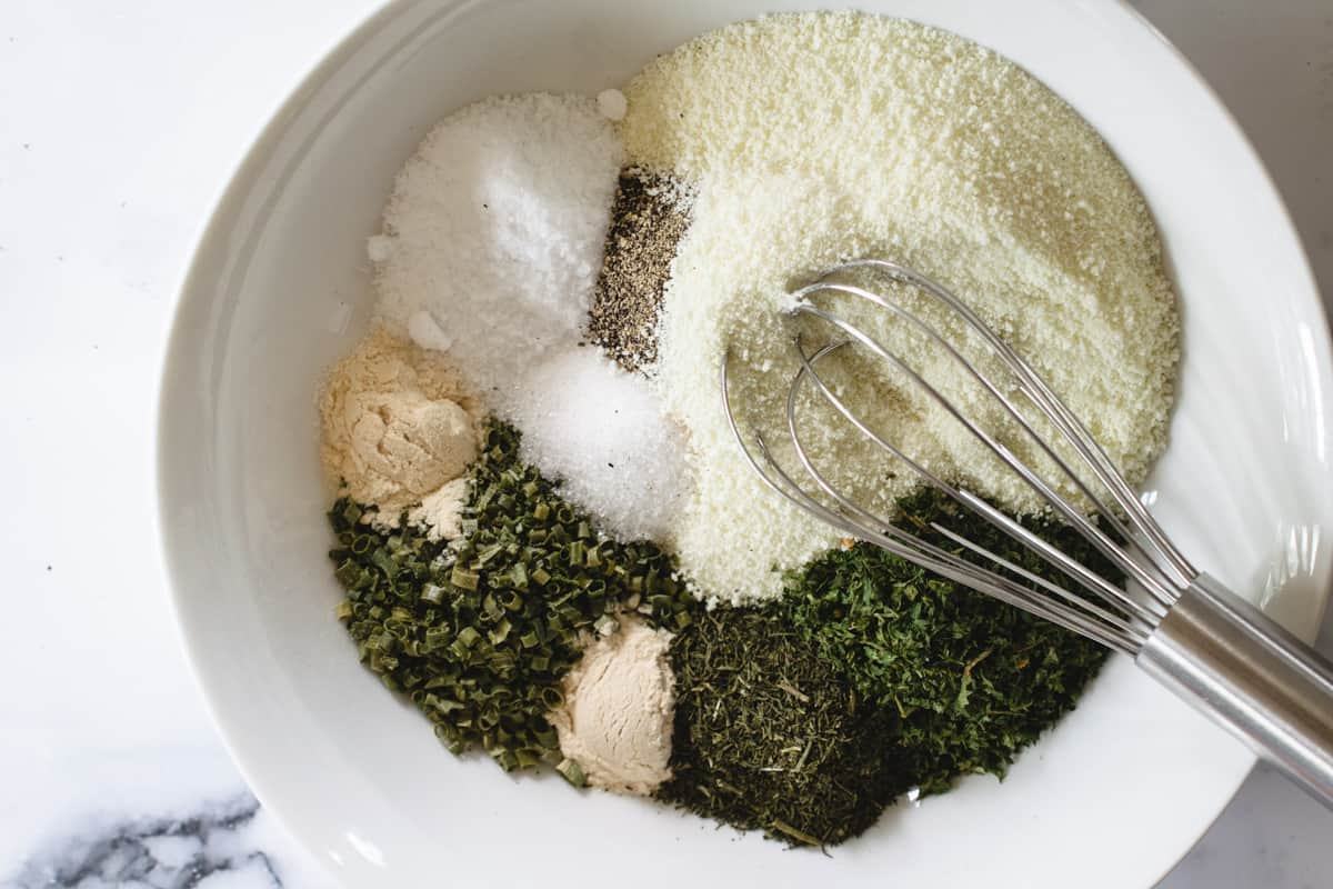 dry ranch mix ingredients in a white bowl with metal whisk