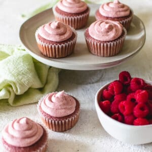 pink raspberry cupcakes on a plate with a bowl of fresh raspberries