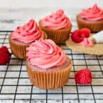Raspberry cupcakes on a cooling rack with fresh raspberries and pink frosting