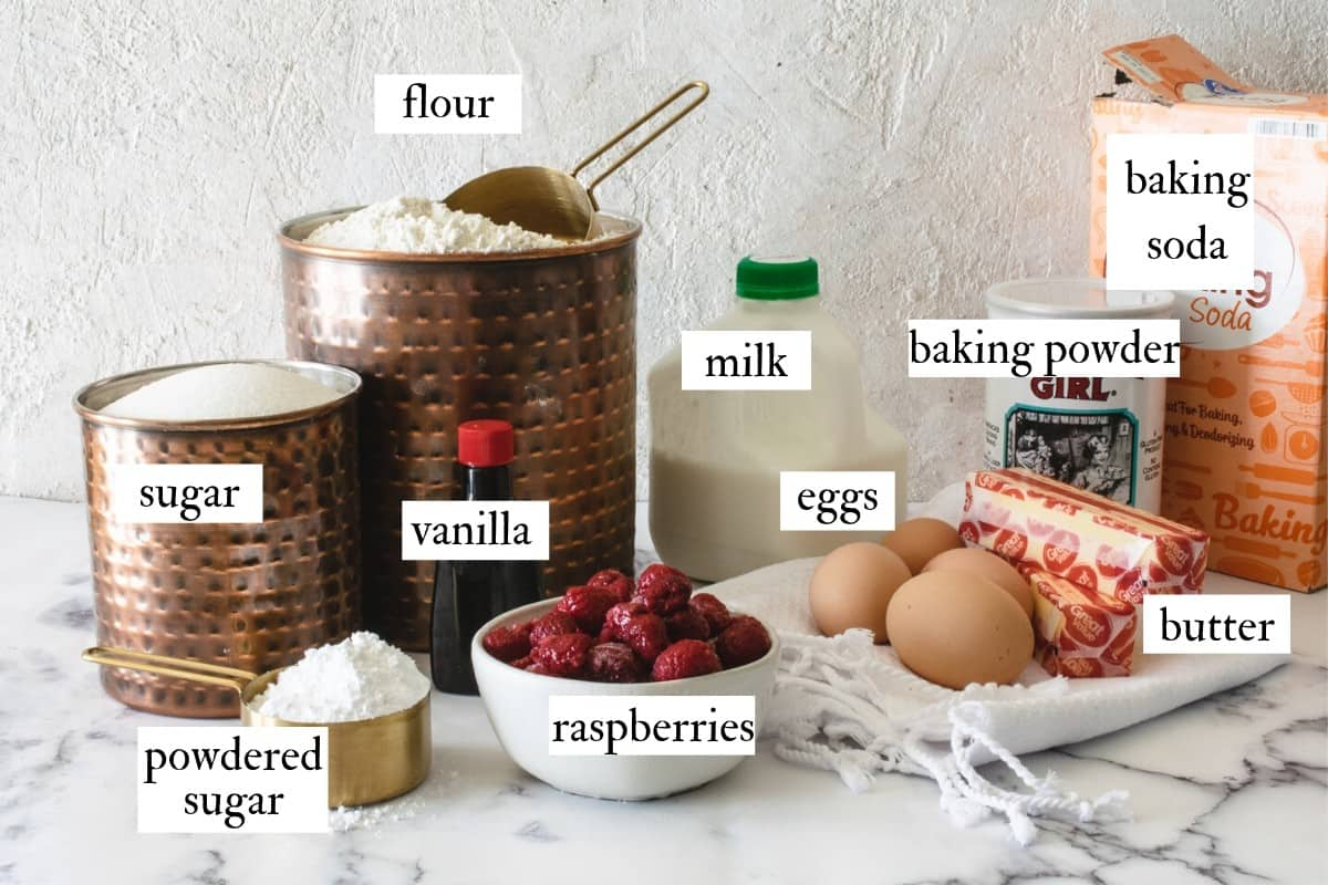 ingredients for making raspberry cupcakes on a white marble counter