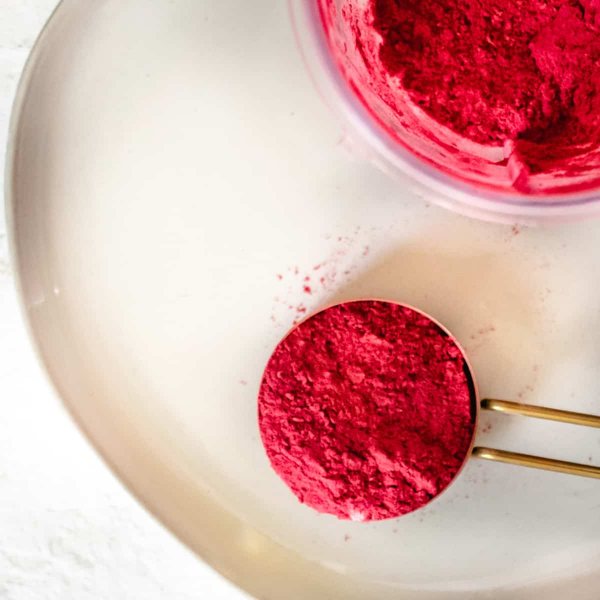 Magenta colored fruit powder in a brass measuring cup.