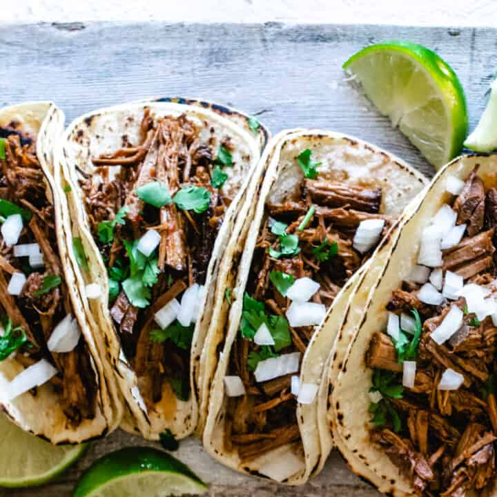 beef barbacoa in corn tortillas with cilantro, onion, and fresh lime