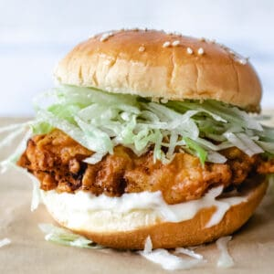 fried chicken patty with mayo and shredded ice burg lettuce on a sesame seed bun