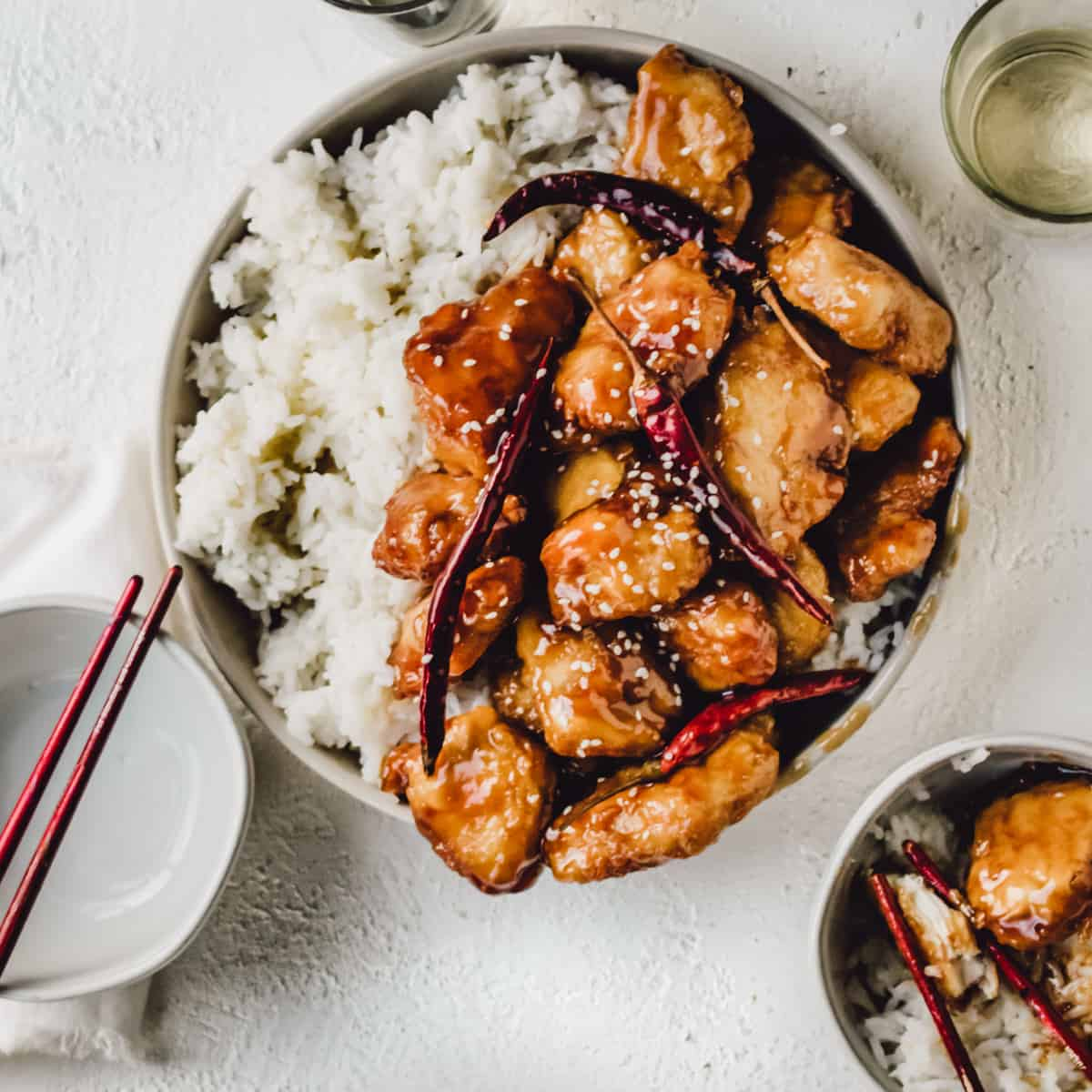 General Tso's chicken with rice in white bowls and red chopsticks.