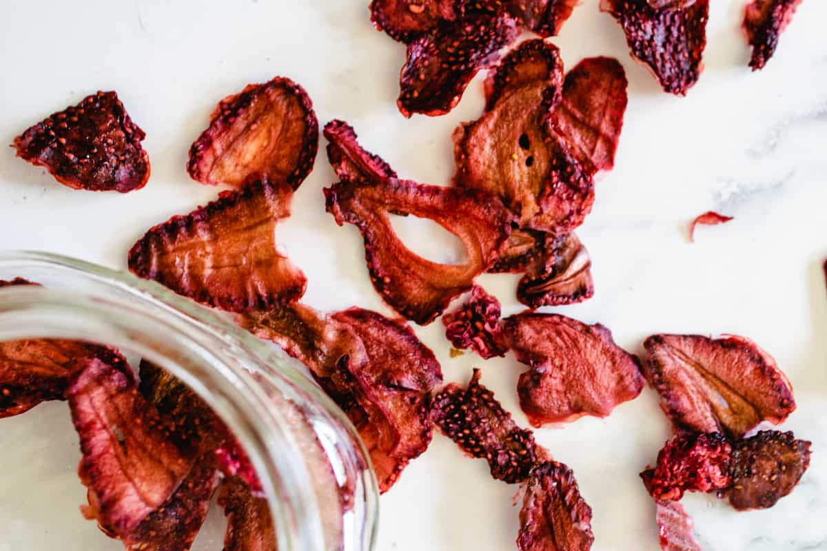 dehydrated strawberries and a jar on a marble counter top