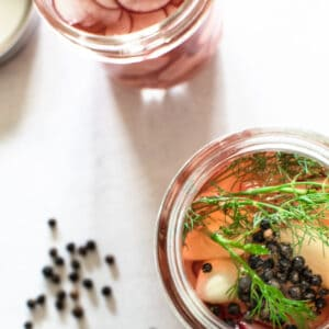 brine poured over radishes and herbs and spices in mason jars