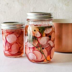 lids on mason jars of sliced radishes and brine