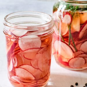 2 jars of pickled radishes, one with added herbs and peppercorns