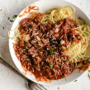 spaghetti with meat sauce, basil ribbons, Parmesan cheese and a fork in a white bowl on white stone counter top