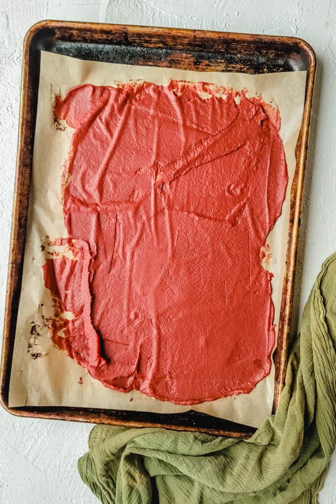A baking sheet with tomato paste spread over it.