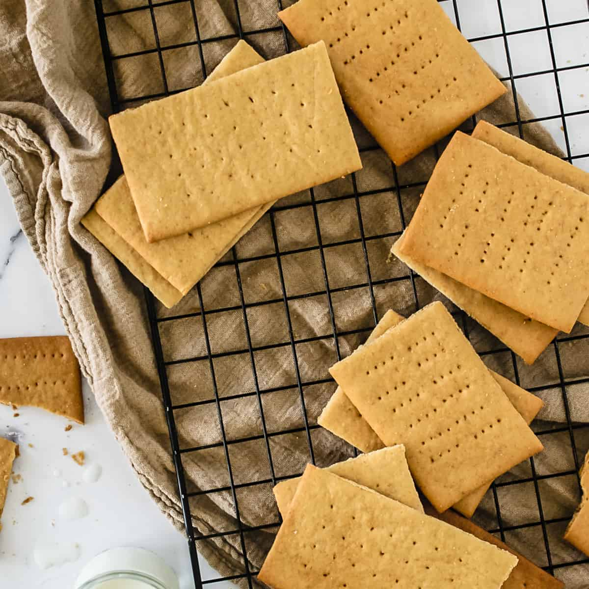 Graham crackers on black cooling rack over taupe towel.