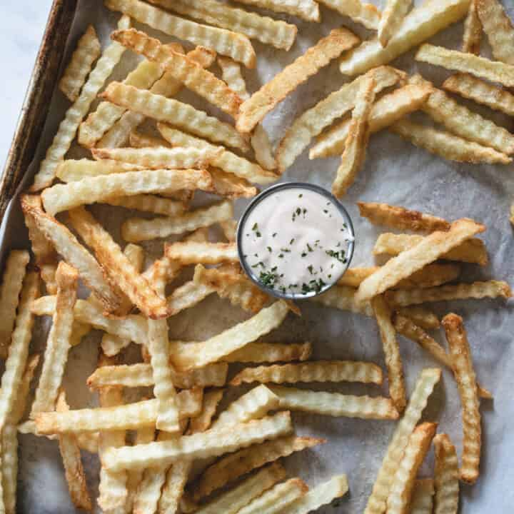 baking sheet lined with parchment paper and fries next to ramekin of fry sauce