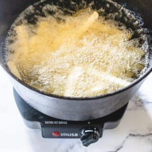 french fries deep frying in a cast iron stock pot of hot oil