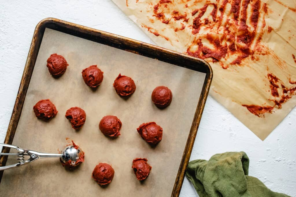 Scooping tomato paste onto a flat tray.