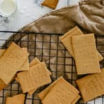 graham crackers on wire rack over taupe cloth with glass of milk and crumbs